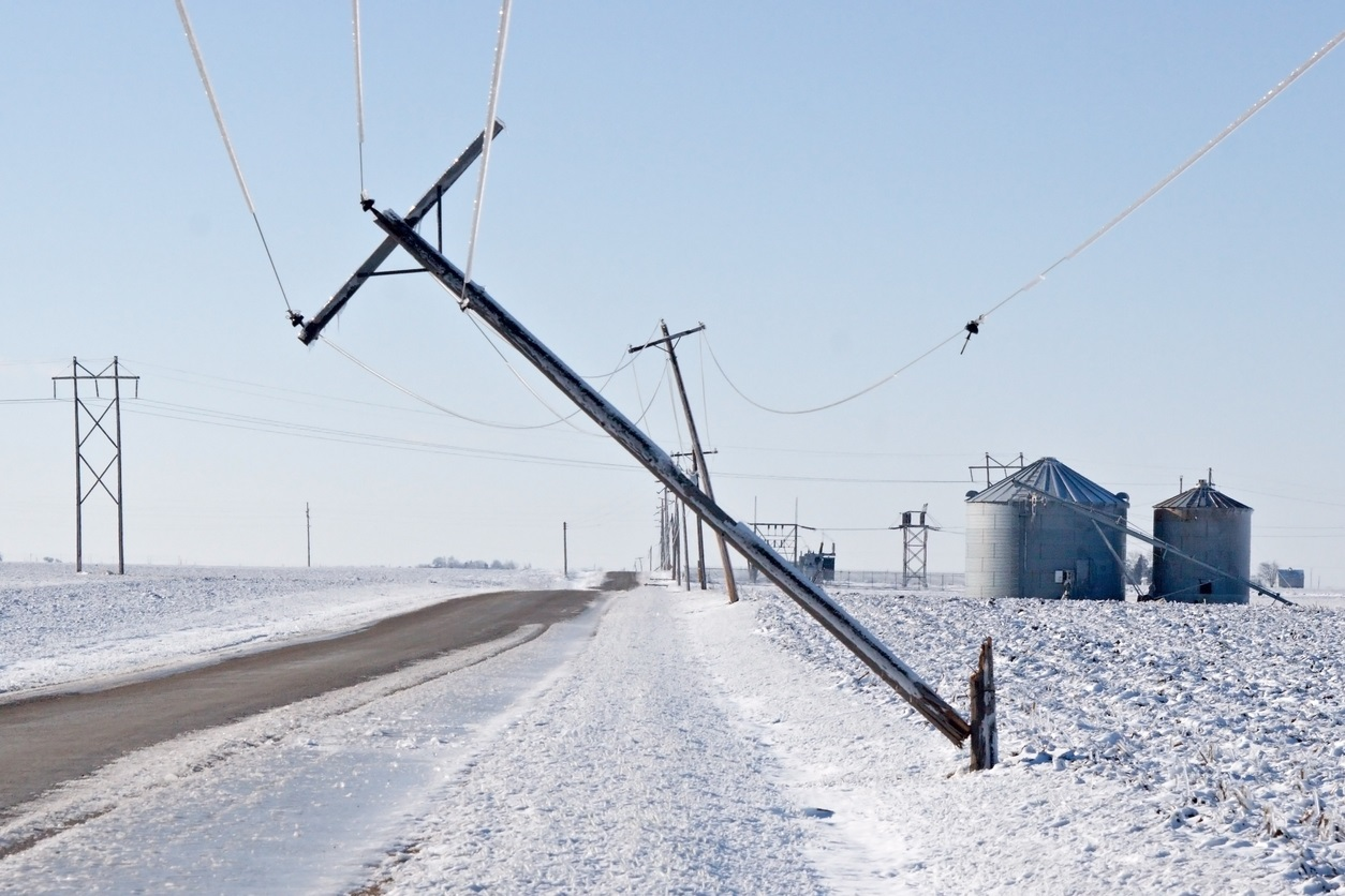 Power lines weighed down by ice cause damage along a country road.