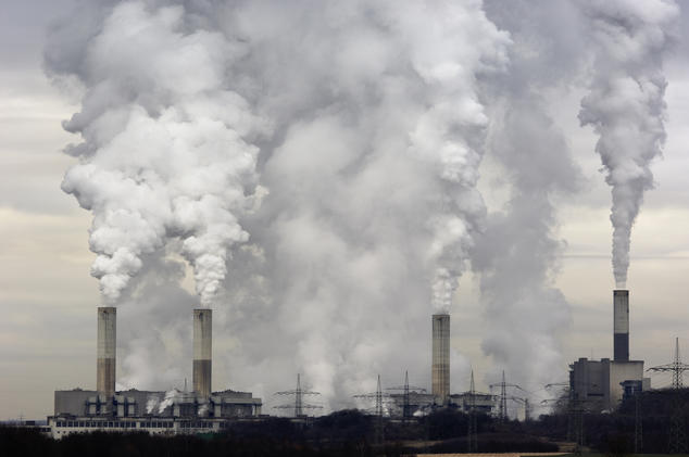 Smokestacks of a coal burning power plant with pollution on a cloudy day.